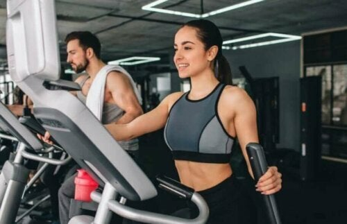woman using the eliptical machine having fun at a gym