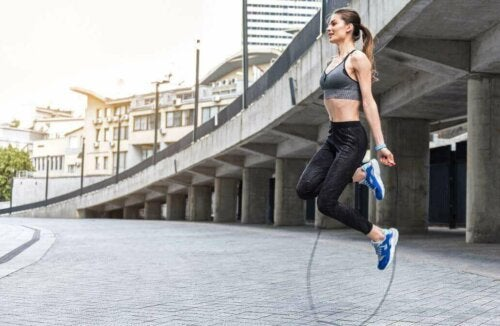 A woman jumping rope outside.