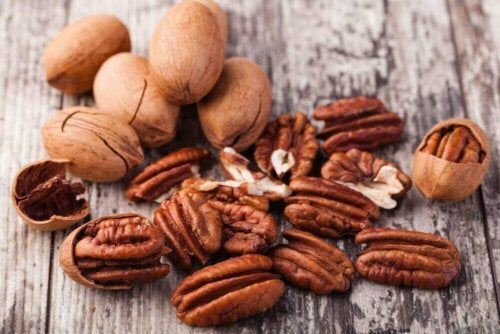 Some pecans on a wooden table.
