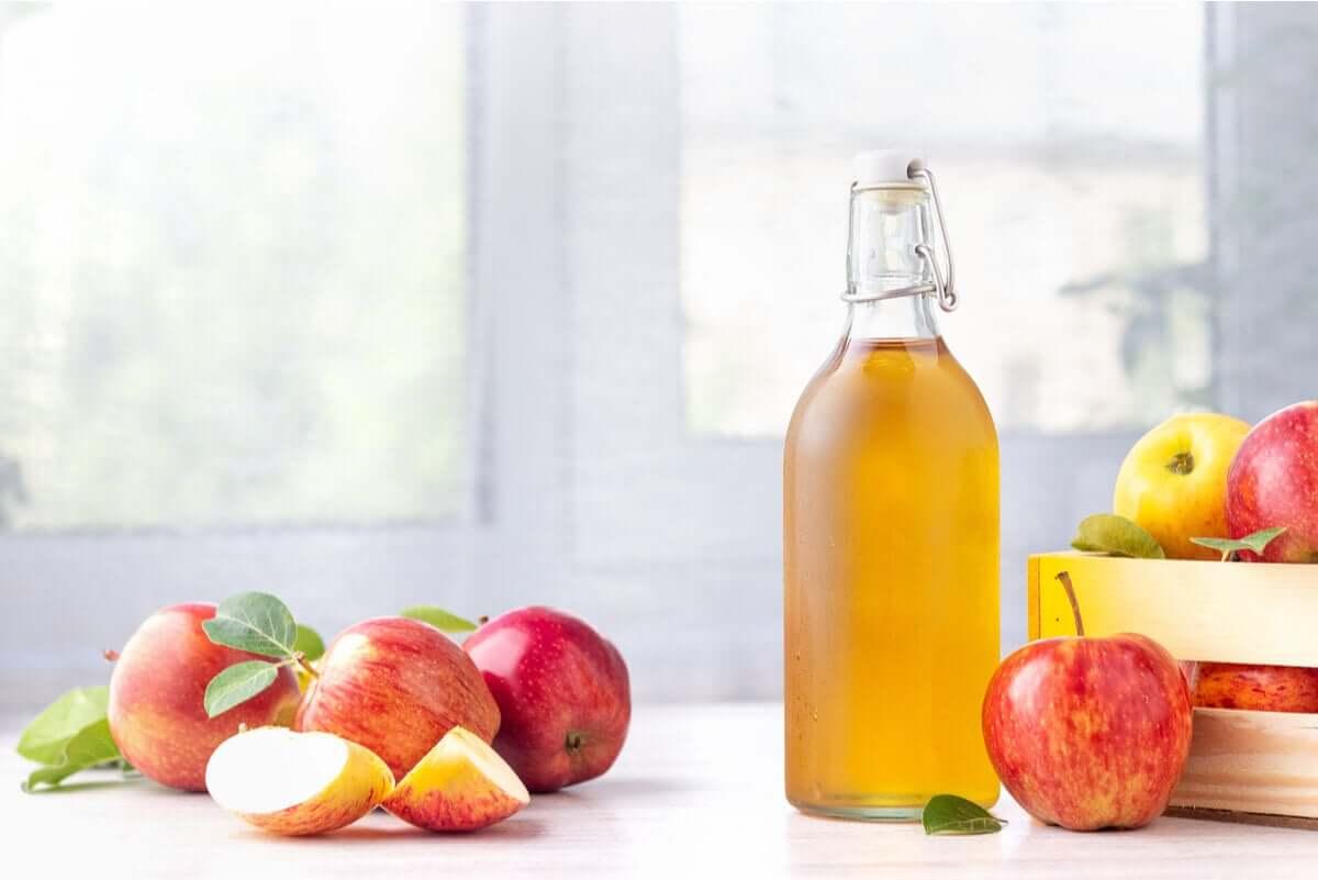 Apples and a glass bottle of apple cider vinegar.