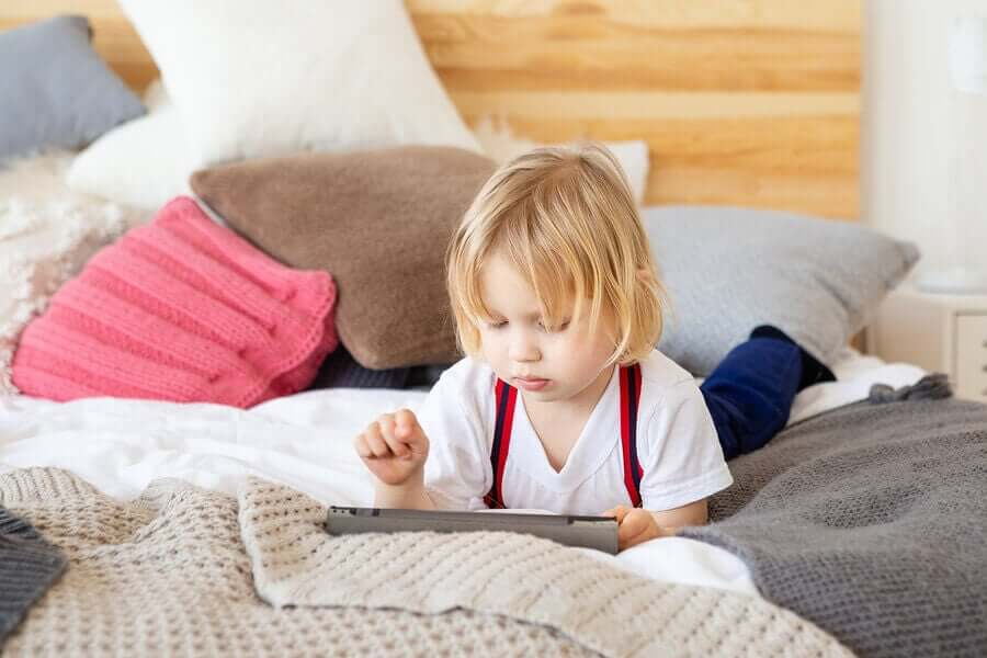 A child looking at a tablet on a bed.