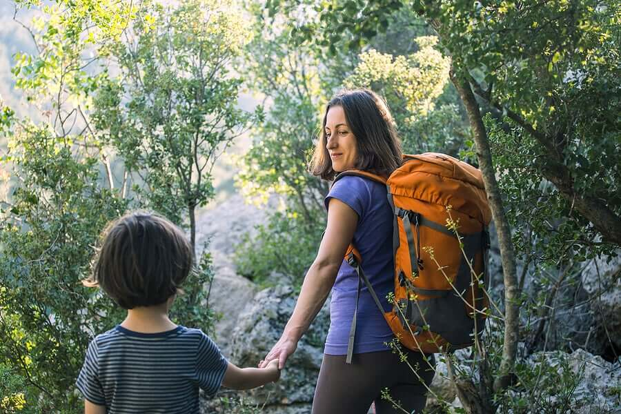 A mother and son hiking in the woods.