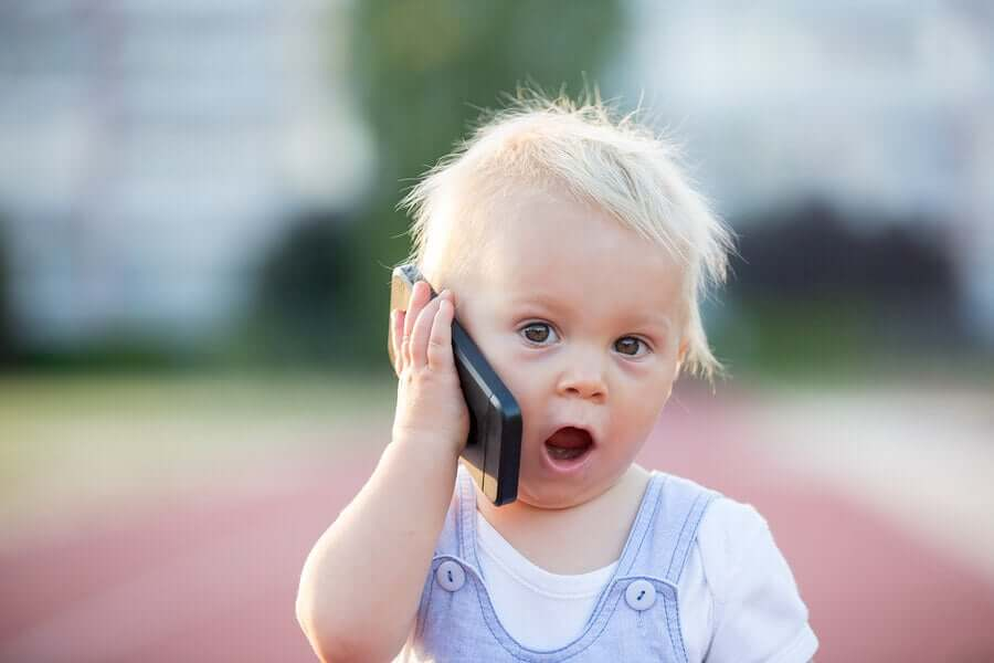 A toddler talking on a cell phone.