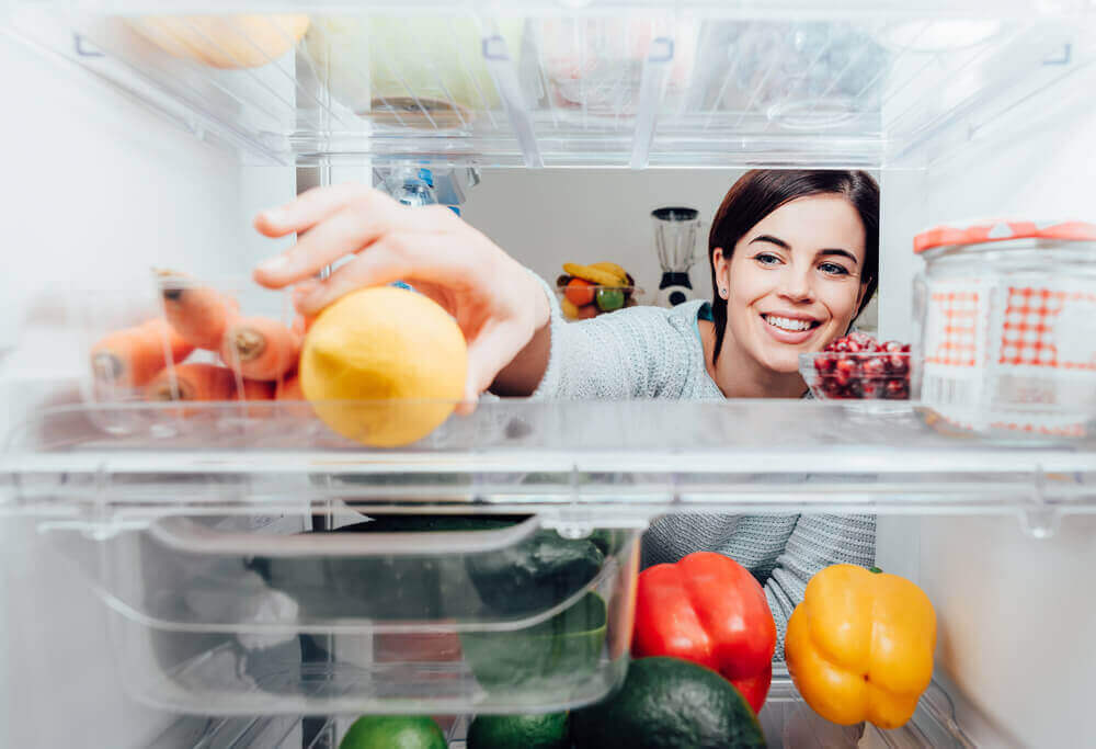 A woman taking a lemon from the fridge.