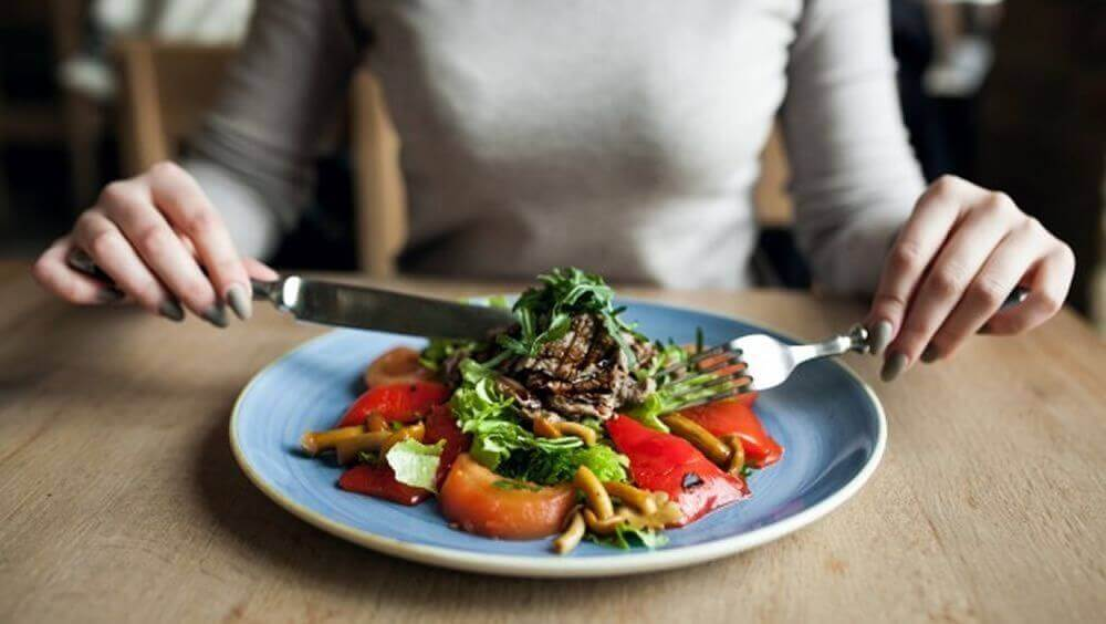 A woman eating a salad for dinner.