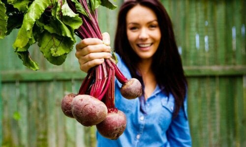 A woman holding a bundle of beets.