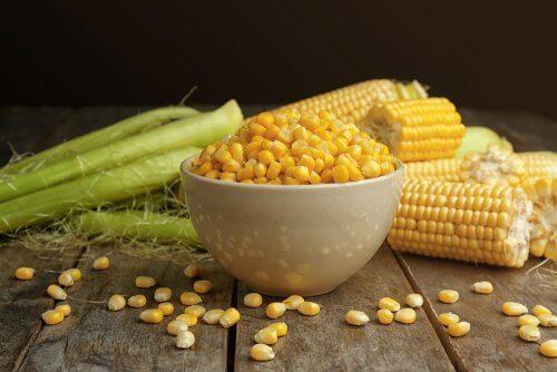 majs i en skål og majskolber ved siden af