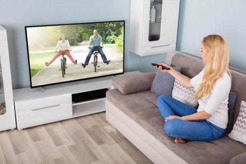 kvinde, der skifter kanal på tv