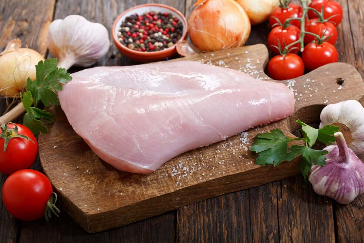 Raw turkey on a cutting board with garlic, spices, tomatoes, and onion.