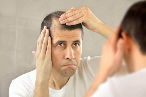 A man who suffers from hair loss looking at himself in the mirror.