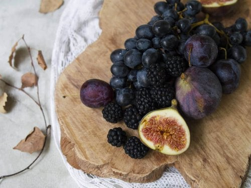 A chopping board with plums, grapes, blackberries and figs.