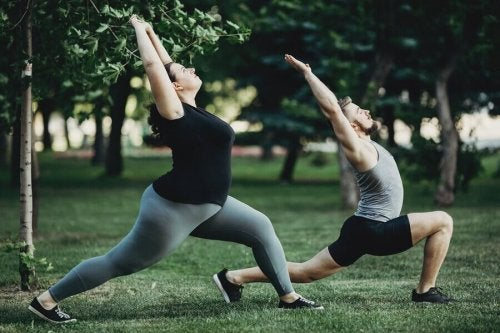 Reduce cholesterol without statins: A man and a woman stretching in the park.