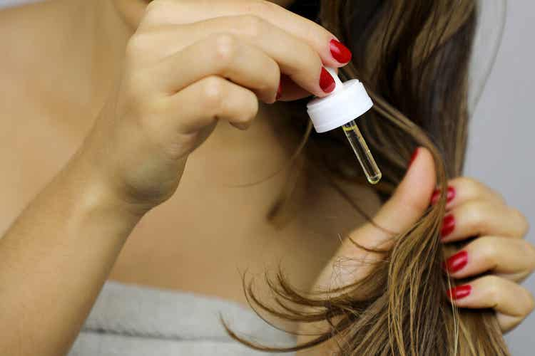 A woman applying argan oil to the ends of her hair.