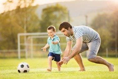 A boy playing soccer with his dad.