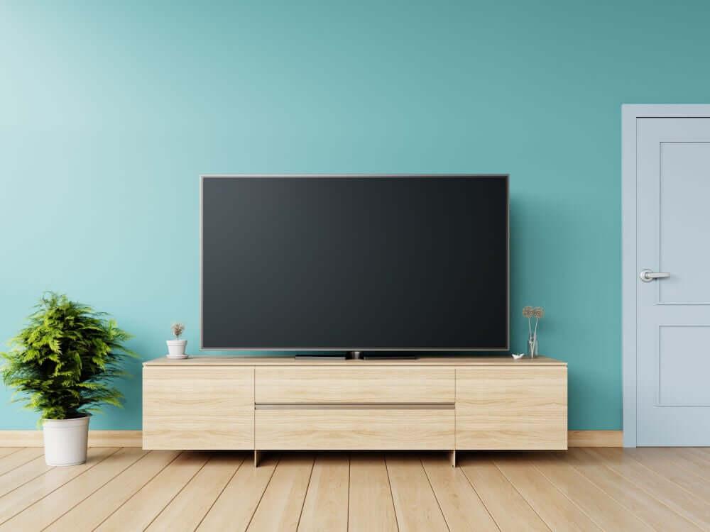 A large flatscreen TV against a teal blue wall.