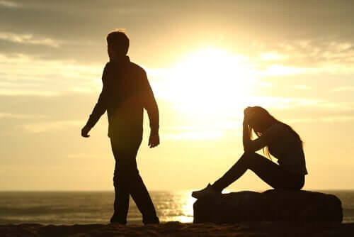 A man walking away from his partner, who's sitting on a log at the beach with her head in her hands.
