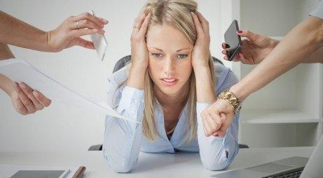 An overwhelmed woman trying to manage stress.