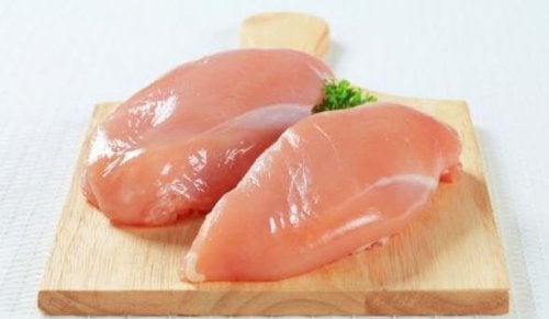 Raw chicken breasts on a chopping board.