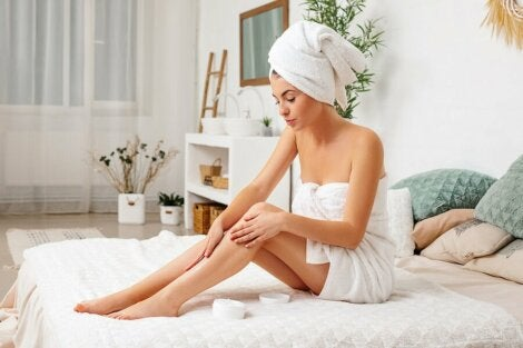 A woman applies cream to her legs.