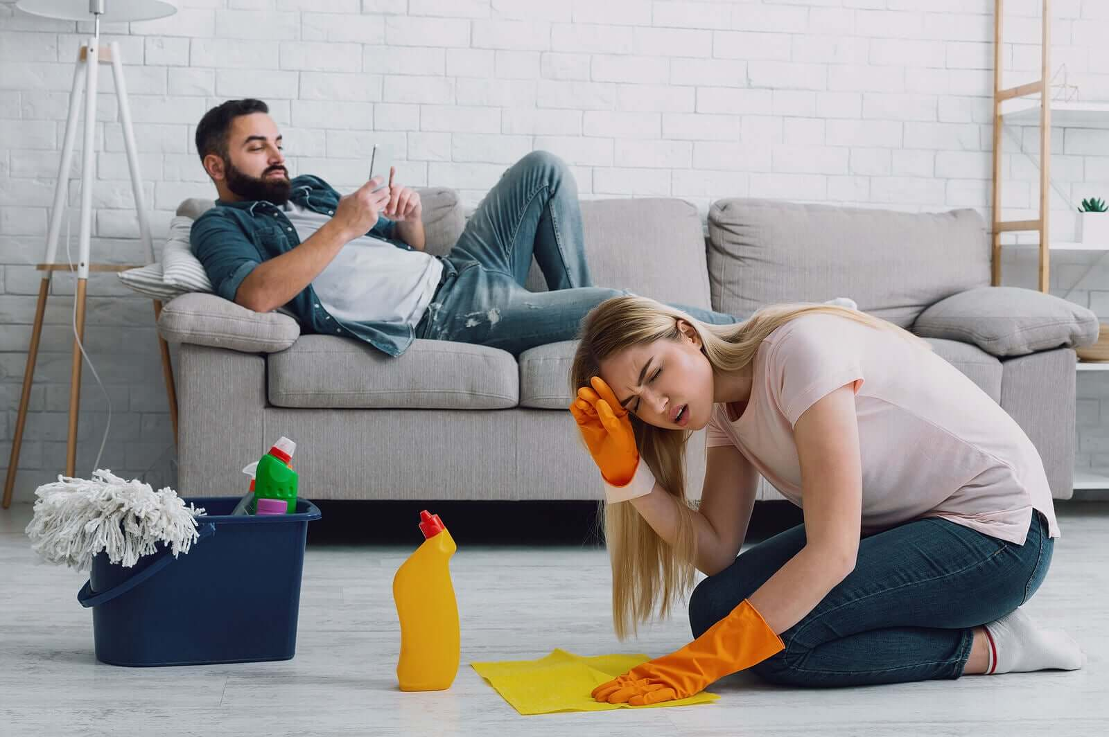a woman looking angry as she cleans the floor and her husband relaxes on the couch.