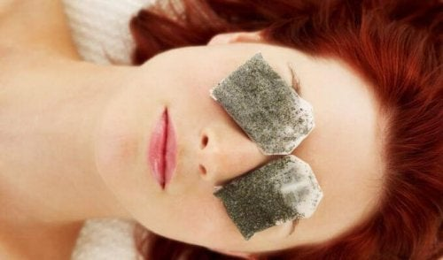 A woman with tea bags over her eyes.