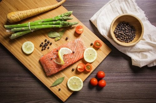 Your child's diet: A chopping board with salmon, asparagus, horseradish, limes, tomatoes, bay leaf and a bowl of black pepper on the side.