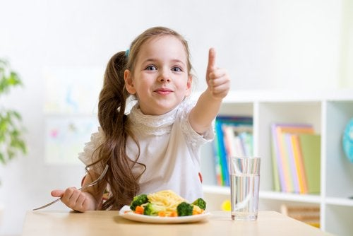 Your child's diet: A girl eating and giving a thumbs up.