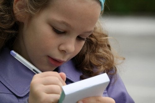 A girl writing on a notepad.