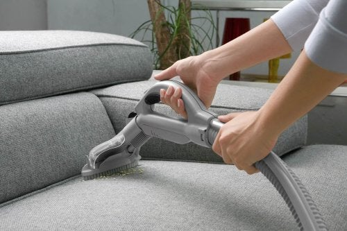 A person vacuuming a sofa.