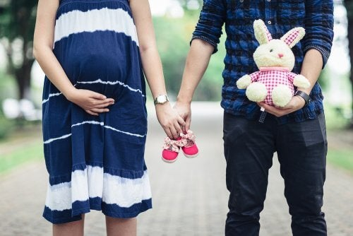 A pregnant woman and a man holding hands, and baby shoes and a stuffed bunny. Both definitely ready to be a parent.