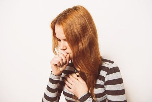 A woman coughing and holding her chest.