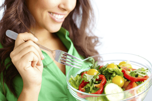 A woman eating a salad.
