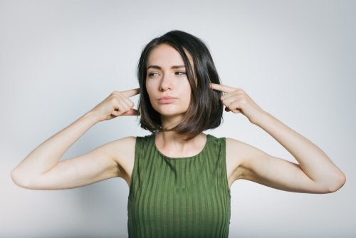 A woman protecting her ears from loud sound.