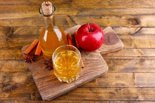 A wooden board with apple cider vinegar and an apple.