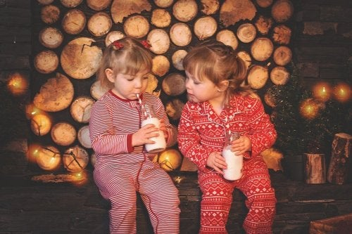 Two girls having a sleepovers and drinking milk.