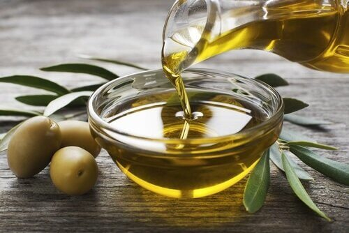 Someone pouring olive oil on a bowl that has olives and it's leaves next to it.