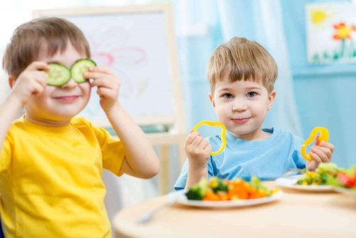 Your child's diet: Two boys eating cucumbers and peppers.