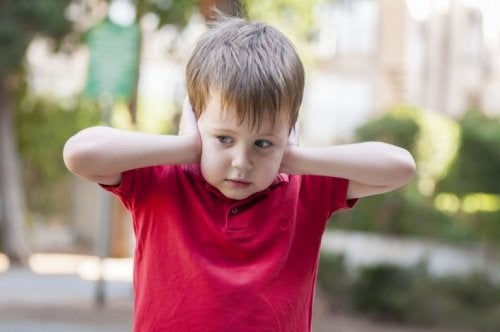 A child covers his ears.