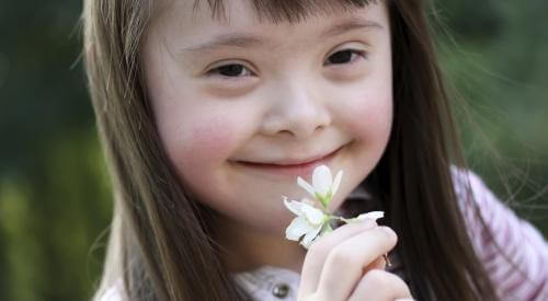 A girl with Down syndrome smelling a flower.