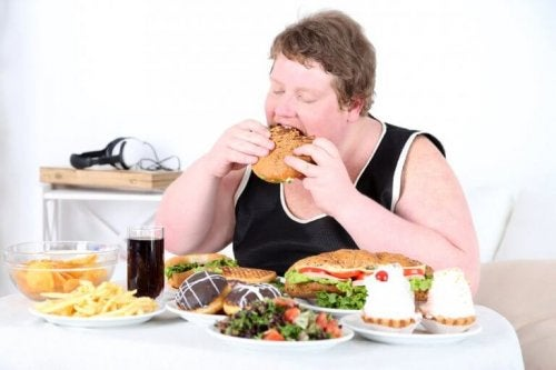Obese man eating lots of food whole buffet on the table unhealthy food hunger and anxiety