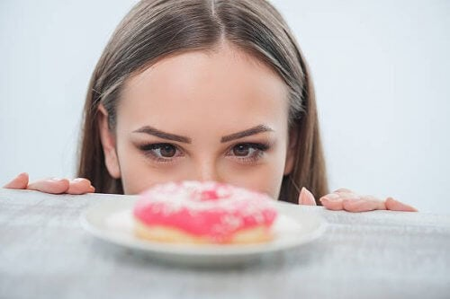 Woman staring at doughnut on table eating because of anxiety instant gratification