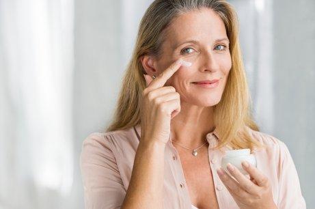 A woman applying a face cream.