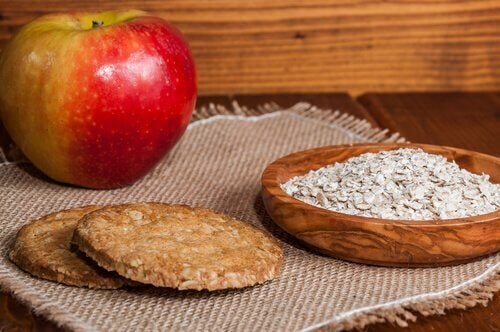 A display of an apple, a bowl of oatmeal and two cookies.