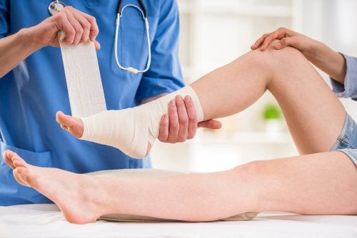 A doctor bandaging a person's ankle.