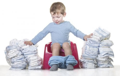 A toddler on a potty surrounded by diapers.