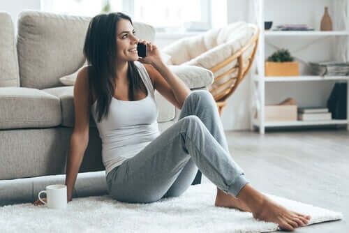 A woman sitting on the floor, talking to her partner on the phone.