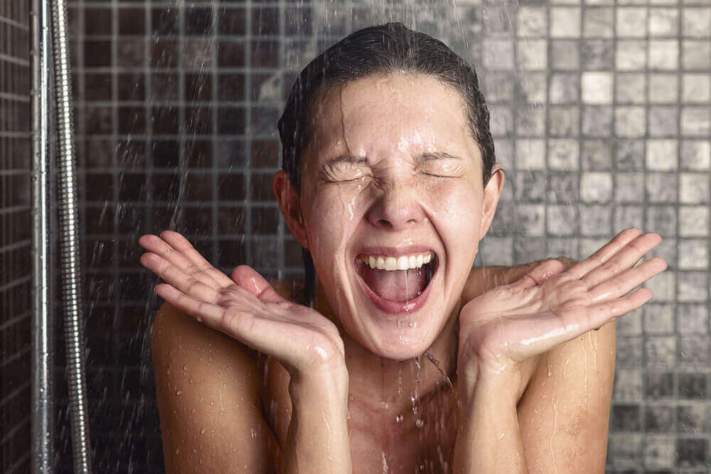 A woman smiling while she takes a cold shower.