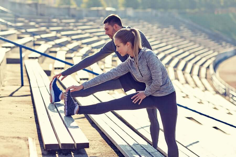 A man and a woman stretching their legs on bleachers.