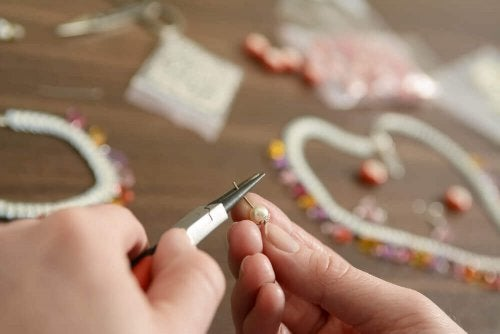 A person making homemade keychains with beads and wire..
