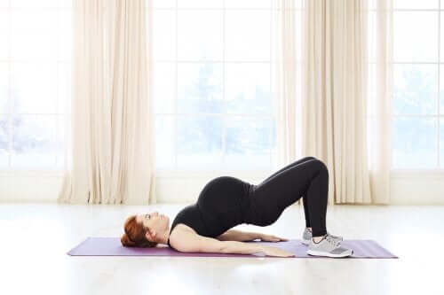 A pregnant woman stretching her back.